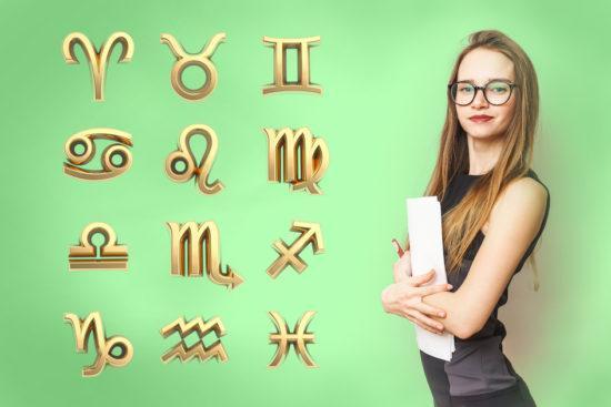 mulher-loira-de-oculos-segurando-livros-sobre-fundo-verde-com-simbolos-dourados-dos-signos-550x367
